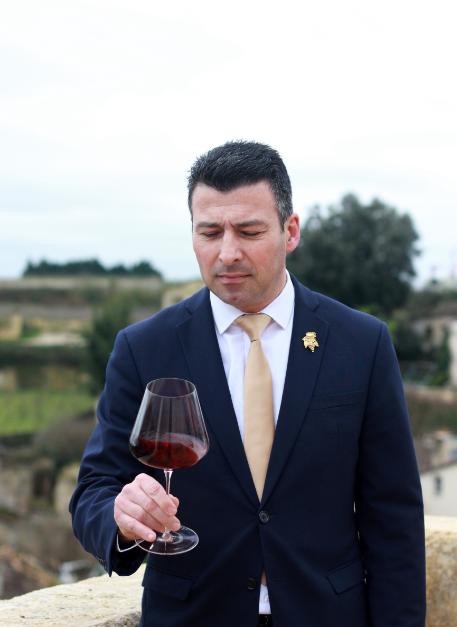 homme en costard tenant un verre de vin rouge